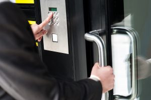 An employee using an access control keypad to enter into the workplace