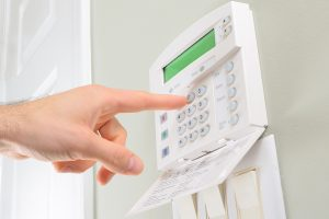 Person presses the buttons on a residential alarm system