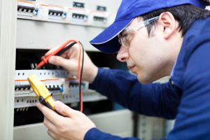 An electrician installs an electrical system at a business